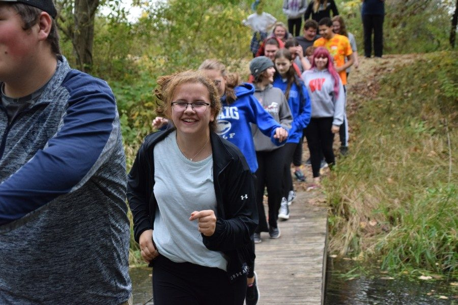 Students jump up and down while crossing a bridge over a small creek at the bottom of Big Hill Park.