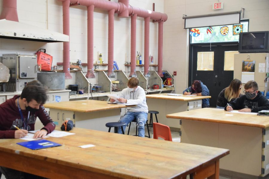 One student per table: art students work on their projects in the arts and metals room.