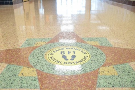 Signs on the hallway floors remind students to remain socially distanced.