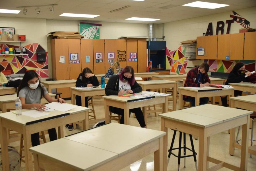 Social distancing in art: Students work at their own table.