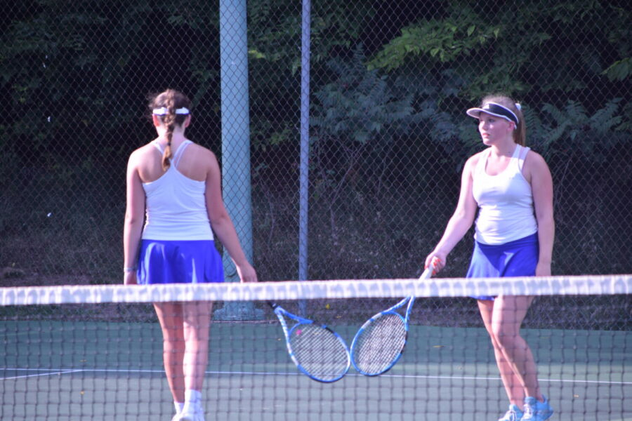 Craigs #1 doubles team of Karyssa Norland (left) and Addison Kooyman touch rackets after a winning point.